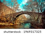 Small photo of Old arch bridge in the autumn forest. Arch bridge in forest. Autumn forest arch bridge. Stone bridge in autumn forest