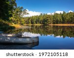 Two Canoes On The Shoreline Of...