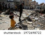 Small photo of Palestinians inspect the damage caused by an Israeli air strike in the town of Khan Yunis, in the southern Gaza Strip, on May 12, 2021