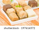 Baklava - Middle Eastern sweet pastry and nuts selection on an orange background. - stock photo