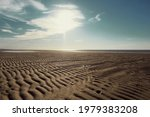 the surface of the sand against a blue sky with white clouds, upward view.