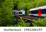 """2 Trains meeting on a viaduct bridge over Lenne River from 19th century on """"Ruhr-Sieg""""-Railway near Werdohl Germany on summer day with green vegetation at the portal of an old tunnel with brick wall."""