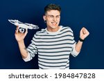 Small photo of Young caucasian boy with ears dilation holding drone screaming proud, celebrating victory and success very excited with raised arm