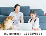 A Mom And Daughter Using Laptop ...