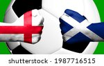 Flags of England and Scotland painted on two clenched fists facing each other with closeup 3d football soccer ball in the background. Mixed media football match game concept
