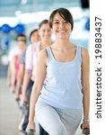 beautiful woman at the gym doing free weight smiling with a group of people behind - stock photo