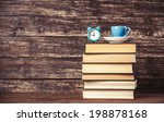 Cup  Clock And Books On Wooden...