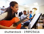Female Pupil Playing Guitar In...