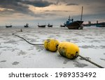 Small photo of Fishery boat mooring bouy on the beach with outdoor low sun lighting.