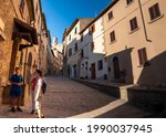 Volterra, Tuscany, Italy. August 2020. The main stone street leading to the historic center is dominated by the bell tower. Tourists observe the fascinating environment. Late summer afternoon.