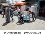 Small photo of Palestinians receive food aid at a United Nations distribution center (UNRWA) in the Rafah refugee camp in the southern Gaza Strip, on June 14, 2021.