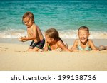 happy kids playing on beach at...
