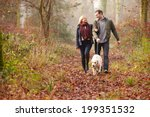 Stock photo couple walking dog through winter woodland 199351532