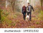 Couple Walking Dog Through...