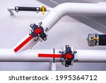 Small photo of White water pipes on a wall background. Branch of the water pipe. Red slewing cranes on white pipes. Water supply system at the enterprise. Concept - supplying the enterprise with aqua.
