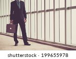 Small photo of Unrecognizable businessman with a briefcase standing in the office building