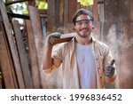 Small photo of Portrait of woodworker or craftsman wearing safety goggles showing thumb up. Caucasian carpenter holding the wooden bar standing in front of plank background. Woodcraft industrial and Hobby concepts