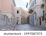 Syros island, Cyclades, Greece. View of emblematic neoclassical buildings at capital of Siros Hermoupolis Empty cobblestone streets pavements and lanterns, cloudy day. Summer destination