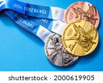 Small photo of April 25, 2021 Tokyo, Japan. Gold, silver and bronze medals of the XXXII Summer Olympic Games in Tokyo on a blue background.