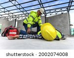Small photo of Accident at work of construction worker at site. Builder accident falls scaffolding on floor, First aid team rushed in to take care prepare helps employee accident. Safety in work concept.