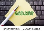 Small photo of asp.net programming language. Word asp.net on paper and laptop