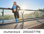 Young atheletic woman going training on urban bridge