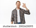Small photo of Alright, well done. Smiling man with red hair, showing OK okay sign and nod in approval, being supportive, say yes, give positive good feedback, agree with you, standing over white background