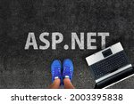 Small photo of asp.net programming language. Legs in sneakers standing next to laptop and word asp.net