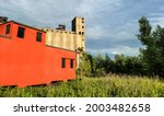 Abandoned red train caboose in green field