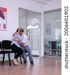 Small photo of Married couple crying in hospital waiting area hearing bad news from doctor, hugging each other. Doctor giving unfavorable test results, stressed man and woman during medical appointment.