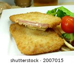 close up of two pieces of cordon bleu whit fried and salad - stock photo