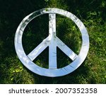 Wide close up of a chrome colored Anti War, Anti Nuclear Peace Sign set against a green grass background with sky and tree reflections.