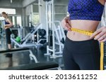Slim woman measuring her waist...
