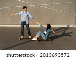 Small photo of Active couple of friends or lovers enjoy ride longboard together on summer city street. Hipster man teaching woman skateboarding. Happy trendy young adults longboarding. Urban leisure activity concept
