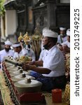 """Small photo of Bali, December 28, 2020 Balinese people playing an authentic Balinese musical instrument called """"Gamelan"""" with Balinese traditional clothes and accessories"""