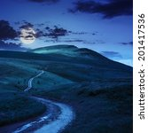 summer landscape. mountain path through the field turns uphill to the sky at night in moon light - stock photo