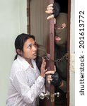 Small photo of Woman holds the door against the aggressor. A criminal in mask of breaking attack the doors of the apartment. Scared woman defense the door of apartment against a man in mask.Defense in the apartment.
