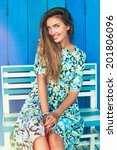 Small photo of Young happy smiling blonde tan woman posing outdoor in achy cafe in summer time wearing vintage floral dress, sitting jn wooden bench at blue background.