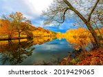 Small photo of Autumn foliage is reflected in the river. Autumn river reflection. Autumn river landscape. River in autumn