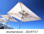 White Parasols On Beachfront...