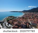An aerial view of a beach with dense buildings under a clear sky in Menton, French Riviera