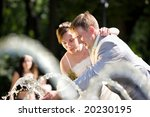 Groom and bride joy in fountain - stock photo