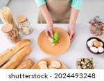 Top angle cropped photo of grandmother prepare homemade meal breakfast put salad lettuce on bread delicious sandwich at home