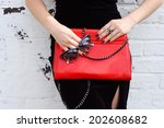 Small photo of Fashionable woman with stylish red clutch , accessories, sunglasses white background