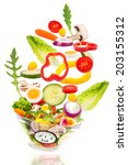 fresh salad falls into a bowl... | Shutterstock . vector #203155312