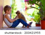 Stock photo excited boy playing with beloved puppy 203421955