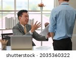 Small photo of Executive boss Asian businessman in suit holding paperwork and blaming young employee with anger and serious gesture look like he comments as disagree or unacceptable for his project work.