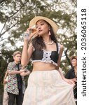 Small photo of A tipsy young woman sips on another a glass of wine while attending a boho themed party with friends outdoors.