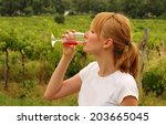 Woman Drinking Wine In Vineyards
