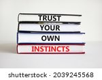 Small photo of Trust your own instincts symbol. Books with words 'Trust your own instincts'. Beautiful white background. Businessman hand. Copy space. Business and trust your own instincts concept.
